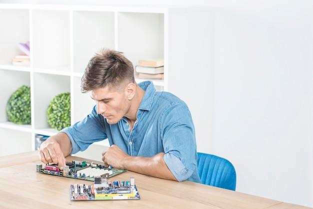 Junger männlicher it-ingenieur, der übt, motherboard zu reparieren