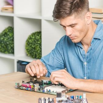 Junger männlicher it-techniker, der motherboard auf tabelle repariert