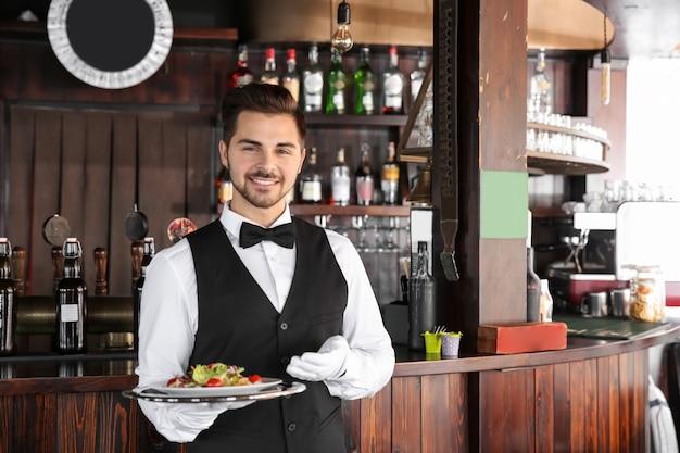 Junger männlicher kellner mit salat im restaurant