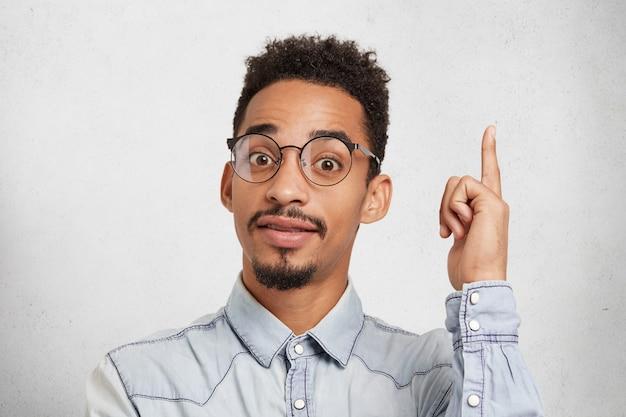 Junger männlicher kluger student trägt brille und jeanshemd, hebt zeigefinger als idee bekommt
