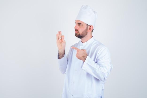 Junger männlicher koch, der auf zigarette in der weißen uniform zeigt und nachdenklich aussieht. vorderansicht.