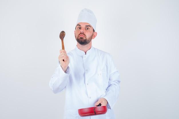 Junger männlicher koch, der bratpfanne und holzlöffel in der weißen uniform hält und nachdenklich schaut. vorderansicht.