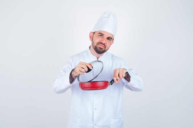 Junger männlicher koch, der deckel von der bratpfanne in der weißen uniform entfernt und neugierige vorderansicht schaut.