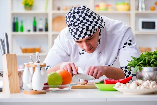 Junger männlicher koch, der in der küche arbeitet