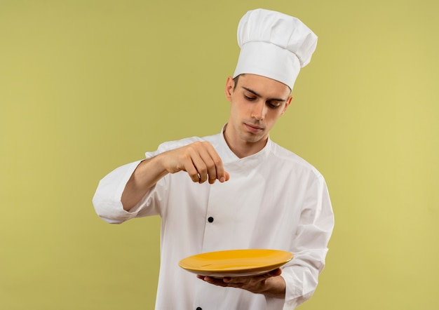 Junger männlicher koch, der kochuniform, die platte schaut, so tut, als würde er salz mit kopienraum verschütten