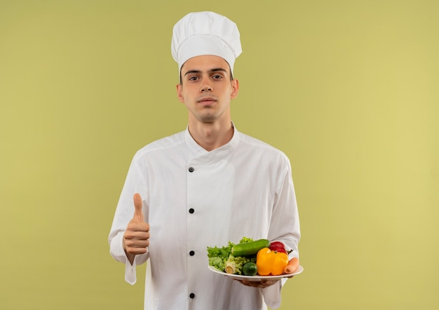 Junger männlicher koch, der kochuniform trägt, die gemüse auf platte seinen daumen oben auf isolierter grüner wand mit kopienraum hält