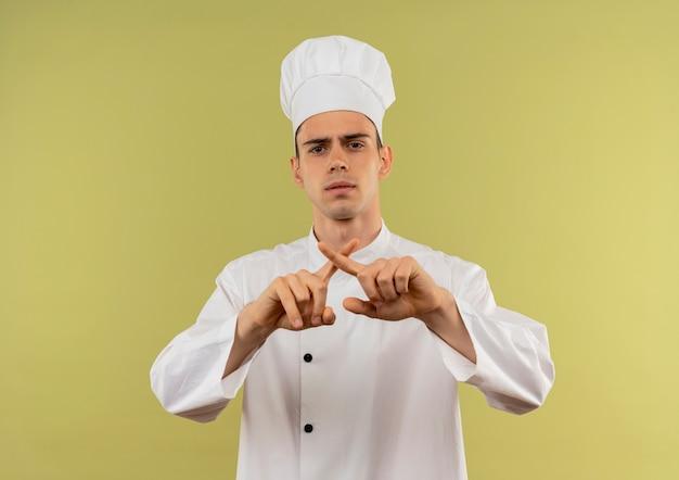 Junger männlicher koch, der kochuniform trägt, die geste nein auf isolierter grüner wand zeigt