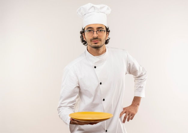 Junger männlicher koch, der kochuniform und brille hält platte und hand auf hüfte setzen