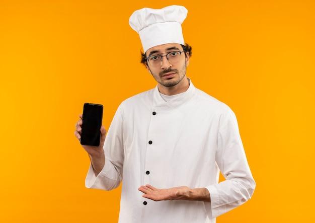 Junger männlicher koch, der kochuniform und brille hält und mit hand zum telefon zeigt