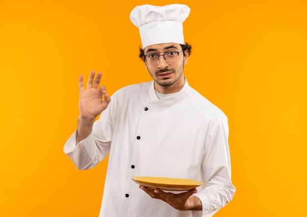 Junger männlicher koch, der kochuniform und brillenteller hält und okey geste zeigt