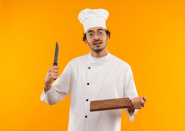 Junger männlicher koch, der kochuniform und gläser hält messer und schneidebrett trägt
