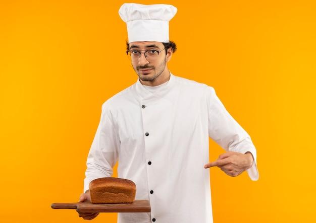 Junger männlicher koch, der kochuniform und gläser hält und auf brot auf schneidebrett zeigt