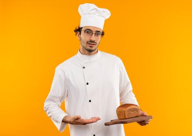 Junger männlicher koch, der kochuniform und gläser hält und mit der hand auf brot auf schneidebrett zeigt