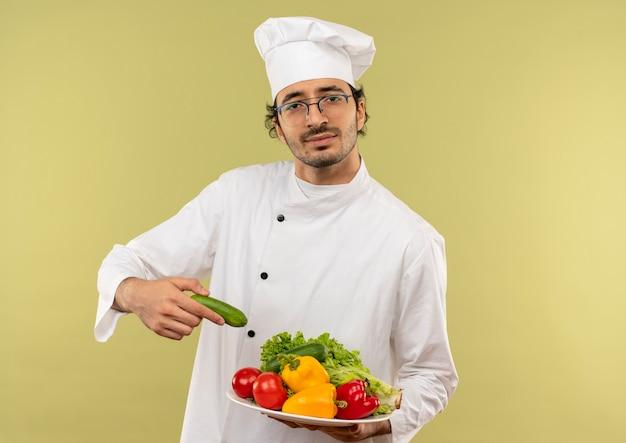 Junger männlicher koch, der kochuniform und gläser trägt, die gemüse auf teller halten