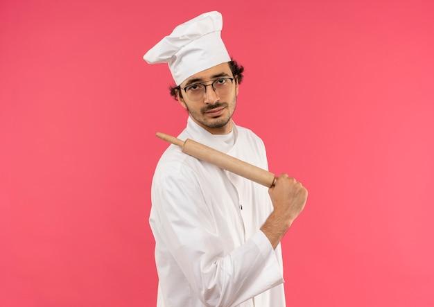 Junger männlicher koch, der kochuniform und gläser trägt, die nudelholz auf schulter setzen