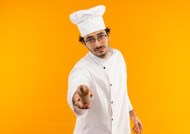 Junger männlicher koch, der kochuniform und gläser trägt, die nudelholz heraushalten
