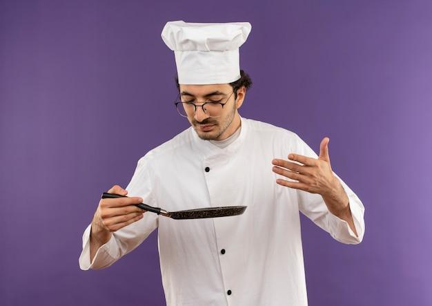 Junger männlicher koch, der kochuniform und gläser trägt, die vorgeben, mahlzeit auf teller in seiner hand auf purpur zu schnüffeln
