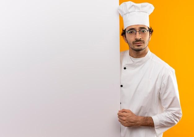 Junger männlicher koch, der kochuniform und gläser trägt, die weiße wand halten