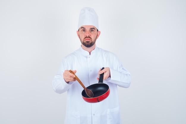 Junger männlicher koch, der leere bratpfanne mit holzlöffel in weißer uniform hält und niedergeschlagen schaut. vorderansicht.