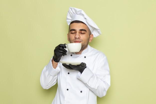Junger männlicher koch der vorderansicht im weißen kochanzug, der dunkle handschuhe trägt und kaffee auf grün trinkt