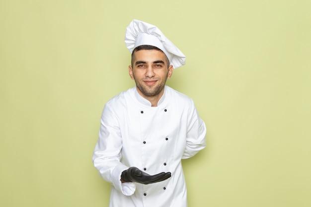 Junger männlicher koch der vorderansicht im weißen kochanzug, der schwarze handschuhe trägt und auf grün begrüßt