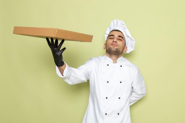 Junger männlicher koch der vorderansicht im weißen kochanzug, der schwarze lederhandschuhe hält box auf grün hält