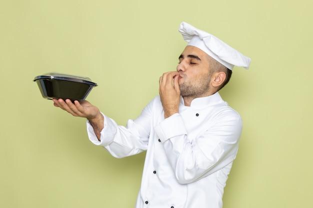 Junger männlicher koch der vorderansicht im weißen kochanzug, der schwarze nahrungsmittelschüssel auf grün hält