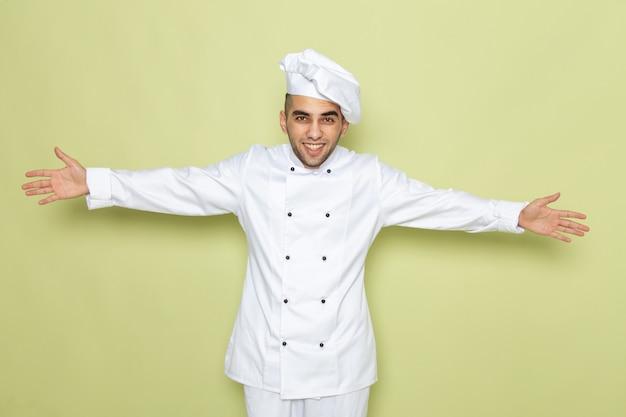 Junger männlicher koch der vorderansicht im weißen kochanzug lächelnd mit weit geöffneten armen auf grün