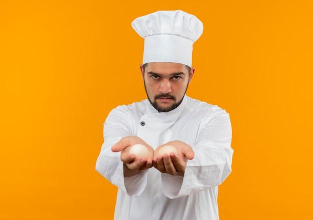 Junger männlicher koch in der kochuniform, die eier in richtung kamera ausstreckt und schaut