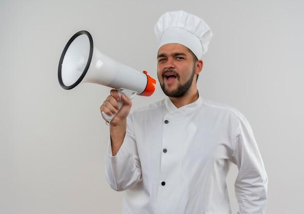 Junger männlicher koch in der kochuniform, die im lautsprechersuchen schreit