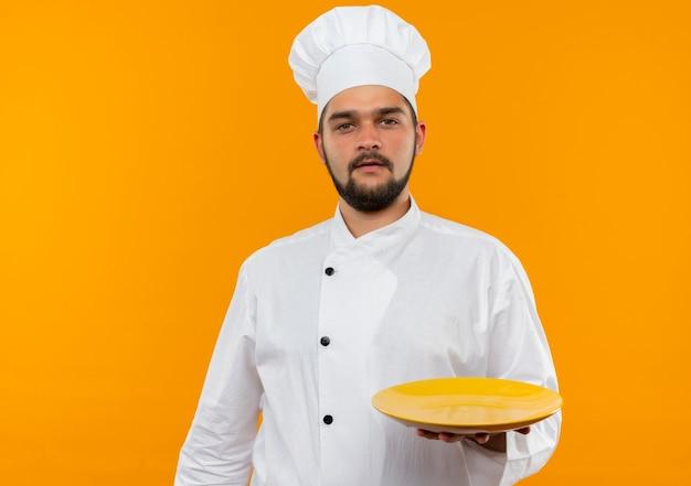 Junger männlicher koch in der kochuniform, die leere platte hält, die auf orange raum lokalisiert schaut
