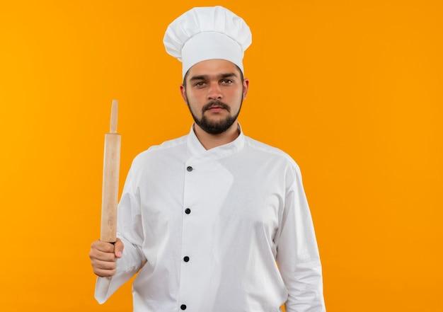 Junger männlicher koch in der kochuniform, die nudelholz hält, das lokal auf orange raum schaut