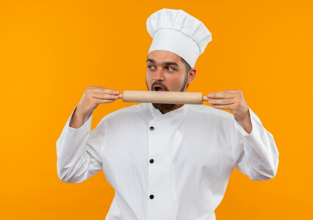 Junger männlicher koch in der kochuniform, die nudelholz hält und versucht, nudelholz zu beißen und seite lokalisiert auf orange raum zu betrachten