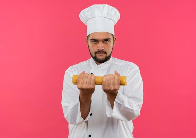 Junger männlicher koch in der kochuniform, die spaghetti-nudeln lokalisiert auf rosa raum hält