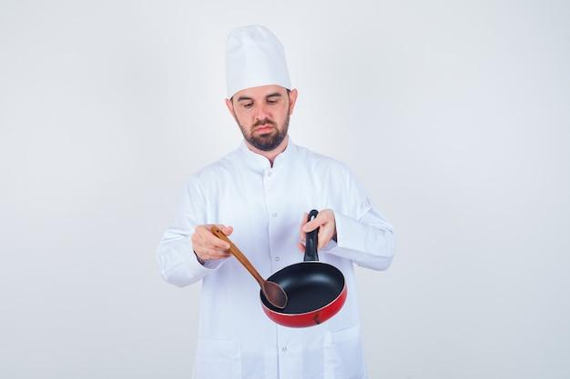 Junger männlicher koch in der weißen uniform, die leere bratpfanne mit holzlöffel hält und niedergeschlagen, vorderansicht schaut.