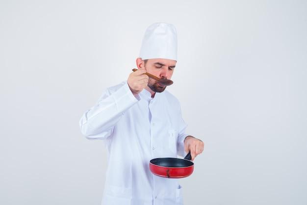 Junger männlicher koch in der weißen uniform, die mahlzeit mit holzlöffel schmeckt und neugierige vorderansicht schaut.