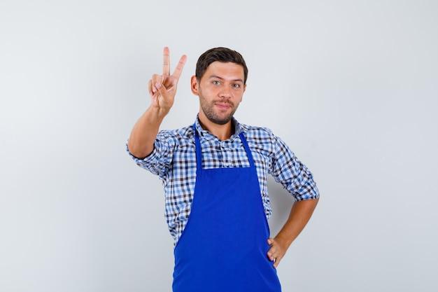 Junger männlicher koch in einer blauen schürze und einem hemd