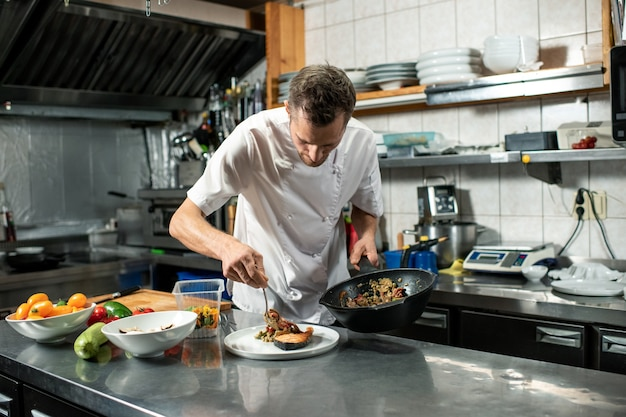 Junger männlicher koch in uniform, der bratpfanne mit gemüseeintopf hält, während er sich mit teller über den tisch beugt und essen auf ein stück gebratenen lachs legt
