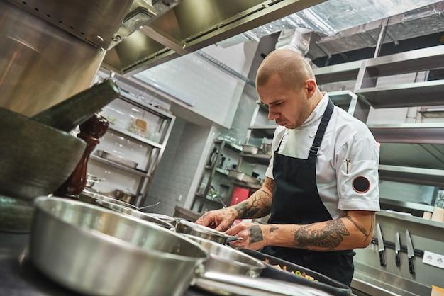 Junger männlicher koch mit mehreren tattoos auf den armen garniert italienische pasta in einer restaurantküche