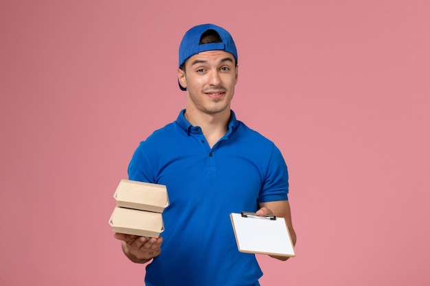 Junger männlicher kurier der vorderansicht im blauen uniformumhang, der kleine liefernahrungsmittelpakete mit notizblock auf hellrosa wand hält