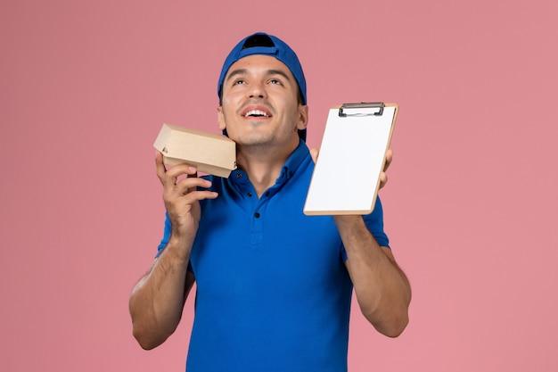 Junger männlicher kurier der vorderansicht im blauen uniformumhang, der kleines lieferfutterpaket und notizblock auf hellrosa wand hält