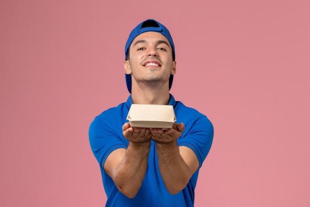 Junger männlicher kurier der vorderansicht im blauen uniformumhang, der kleines liefernahrungsmittelpaket an der hellrosa wand hält