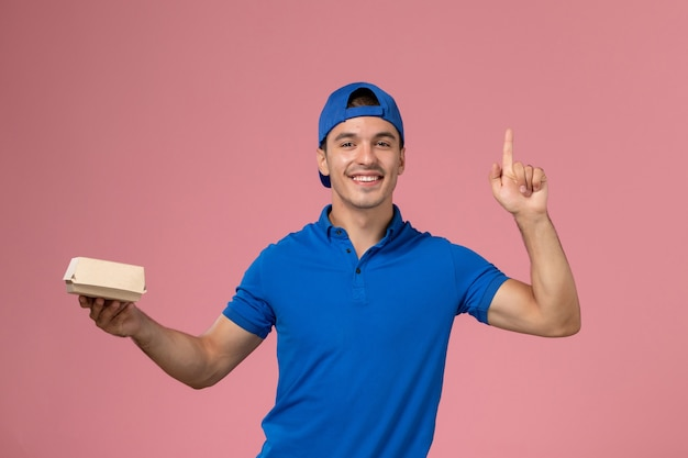 Junger männlicher kurier der vorderansicht im blauen uniformumhang, der kleines liefernahrungsmittelpaket an der rosa wand hält