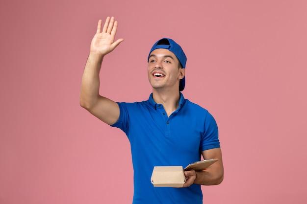 Junger männlicher kurier der vorderansicht im blauen uniformumhang, der kleines liefernahrungsmittelpaket und notizblock hält, die auf hellrosa wand winken