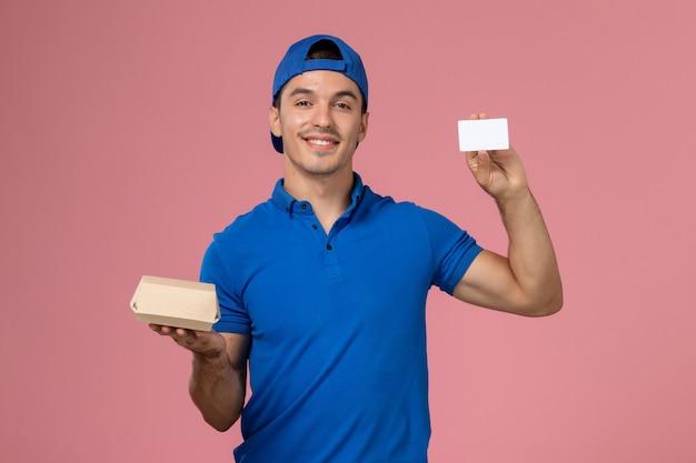 Junger männlicher kurier der vorderansicht im blauen uniformumhang, der kleines liefernahrungsmittelpaket und weiße karte auf hellrosa wand hält