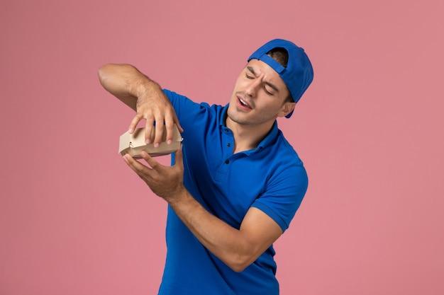 Junger männlicher kurier der vorderansicht im blauen uniformumhang, der lieferung nahrungsmittelpaket hält und versucht, es auf rosa wand zu öffnen