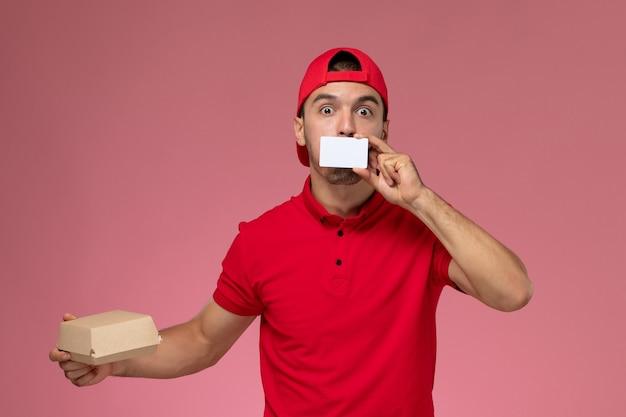 Junger männlicher kurier der vorderansicht im roten uniformumhang, der kleines lieferpaket mit weißer karte auf hellrosa hintergrund hält.