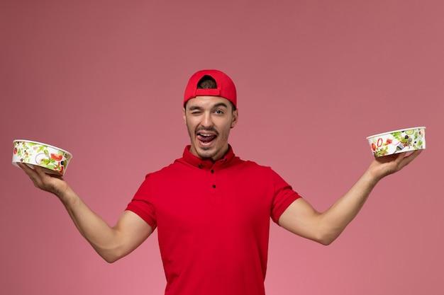 Junger männlicher kurier der vorderansicht im roten uniformumhang, der lieferschalen hält, die auf hellrosa hintergrund zwinkern.