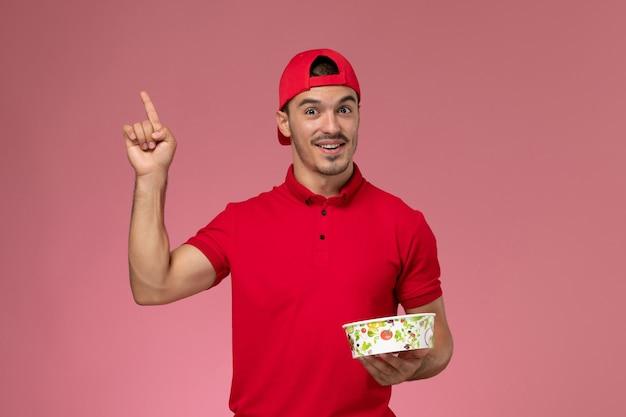 Junger männlicher kurier der vorderansicht im roten uniformumhang, der lieferschüssel auf hellrosa schreibtisch hält.