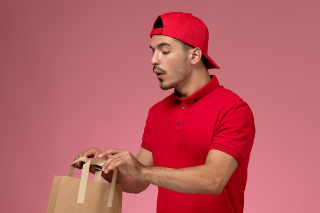 Junger männlicher kurier der vorderansicht im roten uniformumhang, der papiernahrungsmittelpaket hält und es auf rosa hintergrund prüft.